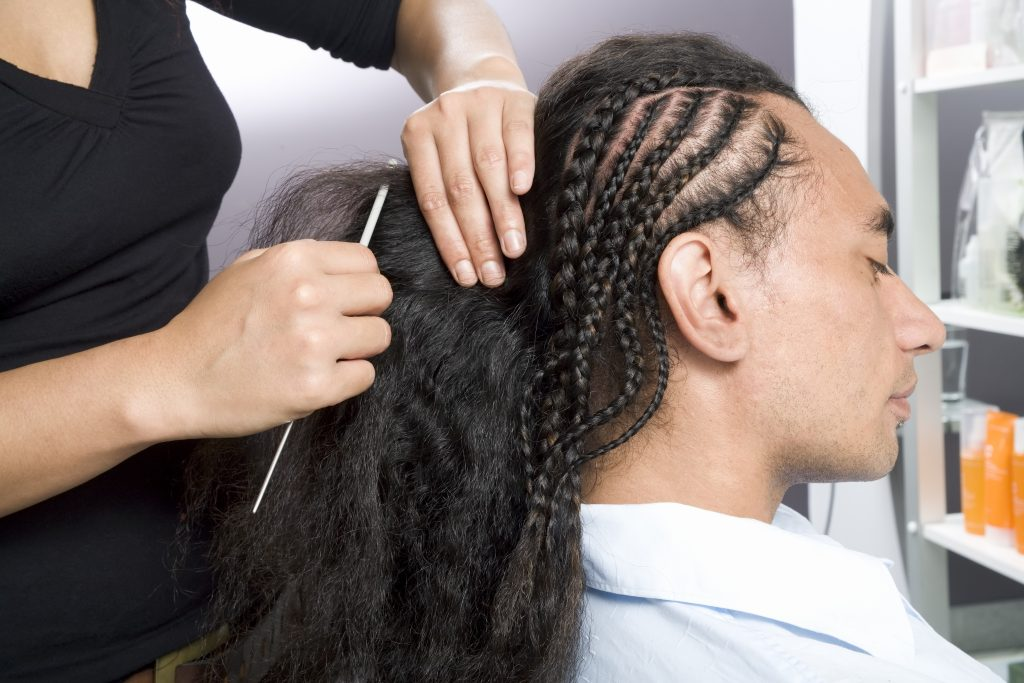 A man getting his hair braided at a salon