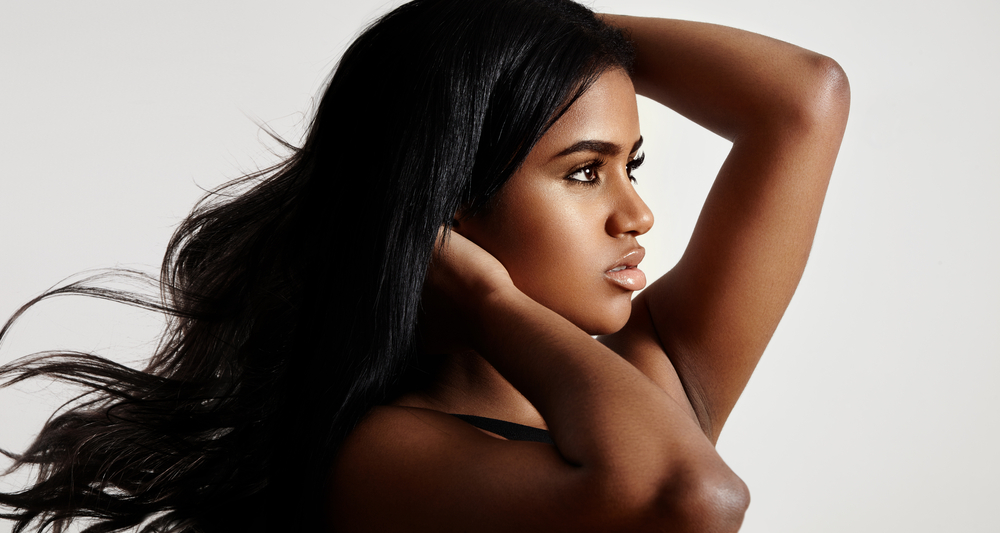 beautiful african american girl with long black hair modeling turned to the side