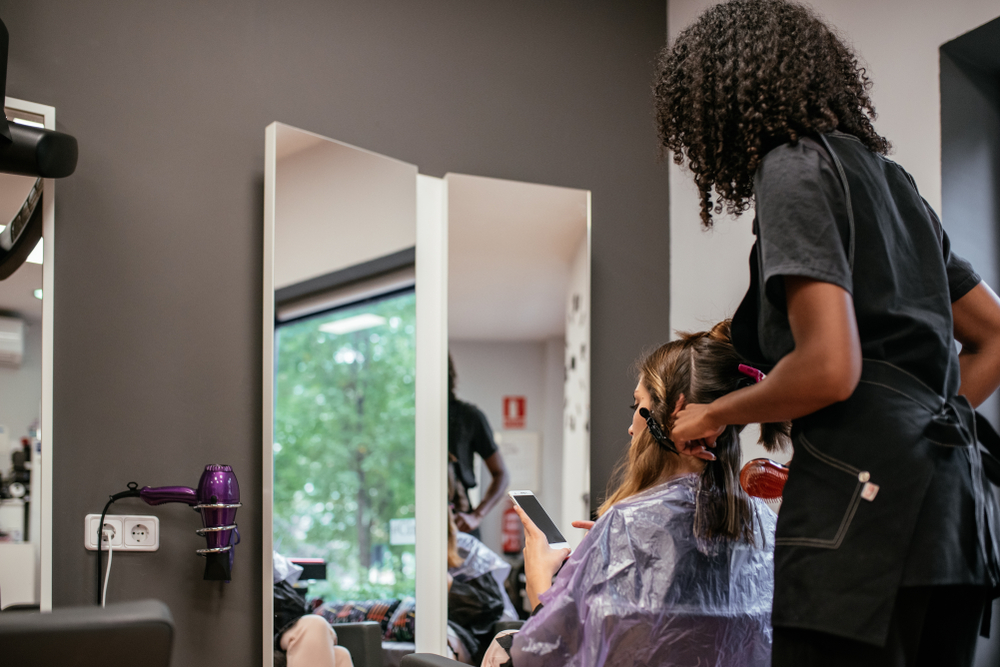 black woman hairstylist doing client's hair in hair salon
